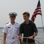 One man in USNA uniform and one guest steering the schooner together