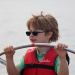 Little boy with sunglasses and orange life vest steering the shcooner