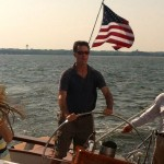 Man with American Flag behind him steering the schooner