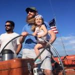 Man holding daughter and steering the schooner