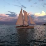 Schooner full of guests under full sunset sail on dark blue water