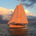 Schooner glowing orange against a dark blue sky and waters at sunset