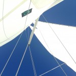 Looking up at pure blue skies through the schooners white sails