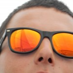 Reflections of the schooner in a man's orange sunglasses