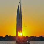 Schooner sailing into a bright yellow sunset with blue waters