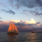 Woodwind with sunset making sails glow orange against a purple sky