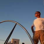 Captain at the helm 0f the schooner on a blue sky day