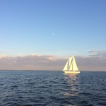 Sun reflecting off of a White Schooner on blue waters against a blue sky