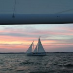 Pink blue and yellow Sunset framing schooner on the water