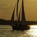 Schooner sailing in sunset with golden glow all around it