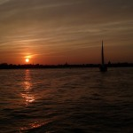 Almost dark sun setting on horizon with sailboat on water