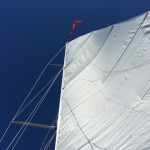 White Sail in a blue sky with red burgee flag flying