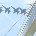 Blue Angels flying over sails of schooner in formation
