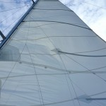 Looking straight up the sail to blue sky with white clouds