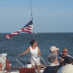 Captain steering schooner and pointing out sights on the way to guests