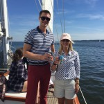 Couple holding up beverages on a beautiful blue sky day sailing