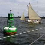 A sailboat racing in the Wooden Boat Regatta sailing around a marker