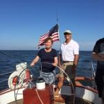 Women steering schooner with guidance from captain