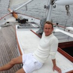 Man in white shorts and sweater leaning back and relaxing on sail