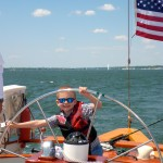 Small boy with sunglasses and life vest smiling as he peaks through the wheel of the schooner