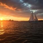Sunset making everything glow orange with schooner sailing by