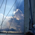 Dark cloud with sun peering out over it looking through sails