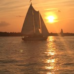 Beautiful sunset turning the sky and the water around the schooner gold