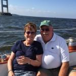 Man and women enjoying beverages while sailing under the bay bridge