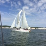 Schooner sailing on blue water with blue sky and white clouds