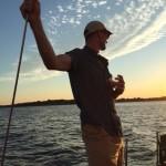 Man holding onto rigging and enjoying beverage sailing at sunset