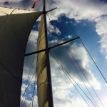Looking up at sails on schooner into a blue sky with white clouds