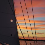 Streaked pink and blue sunset through the schooner sails