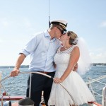 Bride and Groom kissing and holding onto the steering wheel of schooenr
