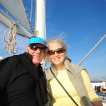 Man and women smiling on a sunny blue sky sail