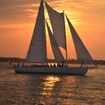 Orange streaked sky and reflecting in waters around schooner sailing