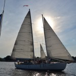American flag and schooner in a picture with sun behind them