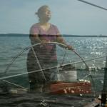 Women steering the schooner with water reflection all around her