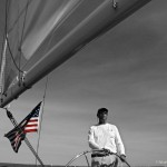 Black and white of captaining boat with a red white and blue flag