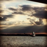 Sailboat with a horse silhouette spinnaker on it and dark clouds behind it