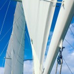White sails, rigging and mast against a bright blue sky