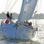 Guests and crew on schooner flying over the water sailing