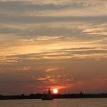 bright red ball of sun behind schooner sailing