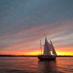 Streaked Blue, pink and orange sky reflecting on water around the schooner