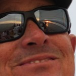 Face of man smiling with sunset reflected in his glasses