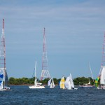 Sailboats with colorful sails sailing in front of red and white towers