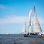 The schooner sailing among dozens of sailboats on the bay