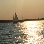 Two schooners sailing in waters reflecting the sun