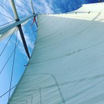 Looking straight up the schooner sails in to blue and white sky