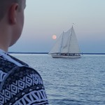 Man looking out over water at Schooner with Moon rising above it