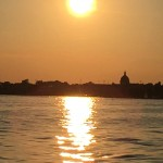 Bright yellow large sun shining over Annapolis and water